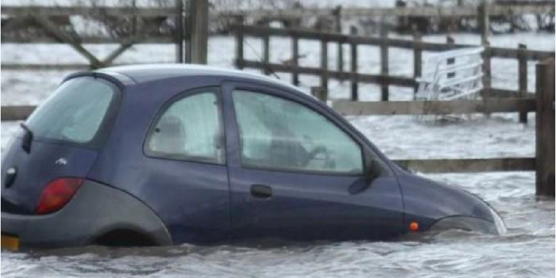 Small car stuck in severe floods.