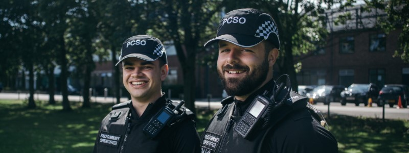Two male police community support officers smiling